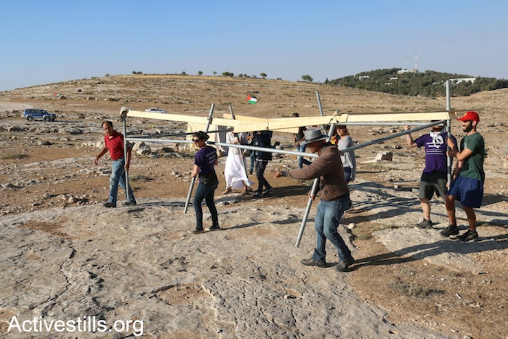 Activists build a new tent after Israeli soldiers dismantled the Sumud Freedom Camp, Sarura, West Bank, May 24, 2017. (Ahmad al-Bazz/Activestills.org)