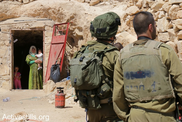 Israeli soldiers stand in front of a cave in Sarura, where a Palestinian family lives, during the second IDF raid on Sumud Freedom Camp, May 25, 2017. (Ahmad al-Bazz/Activestills.org)