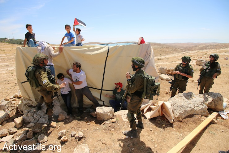 Activists try to prevent the Israeli army from dismantling one of the camp's tents during the second raid on the Sumud Freedom Camp, Sarura, West Bank, May 25, 2017. (Ahmad al-Bazz/Activestills.org)