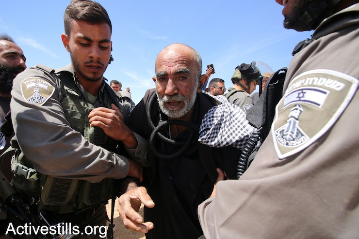 Israeli soldiers evacuate a Palestinian elder from the Sumud Freedom Camp in order to dismantle one of the protest camp's tents, Sarura, West Bank, May 25, 2017. (Ahmed al-Bazz/Activestills.org)