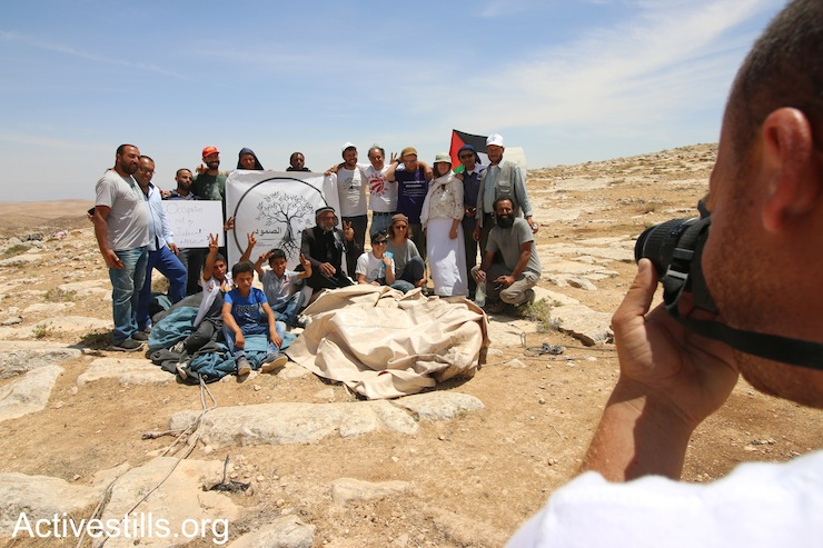 Palestinians, Israelis, and diaspora Jewish activists pose for a photograph to celebrate the return of two tents after they were confiscated by the army in the Sumud Freedom Camp, May 25, 2017. (Ahmad al-Bazz/Activestills.org)