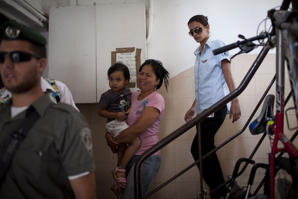 Population and Immigration Authority agents arrest a Filipina and her daughter in south Tel Aviv, taking them to a deportation detention facility at Ben-Gurion Airport prior to their deportation, August 16, 2011. It was the first documented arrest in which a child of foreign immigrant workers, born, raised and educated in Israel was arrested and deported. (Oren Ziv/Activestills)