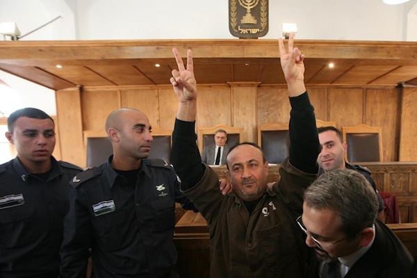 Palestinian leader Marwan Barghouti is escorted in handcuffs by Israeli police into Jerusalem's Magistrate Court, January 25, 2012. Barghouti was sentenced to life imprisonment in 2002 for organizing violent attacks during the Second Intifada in 2000 (Flash90)