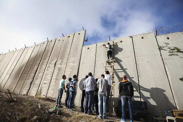 Palestinians try to climb over the separation wall at the Qalandyia checkpoint between the West Bank city of Ramallah and Jerusalem on their way to attend the last Friday prayers in Jerusalem's al-Aqsa mosque during Muslim holy month of Ramadan, Friday, July 1, 2016. (Photo by Flash90)