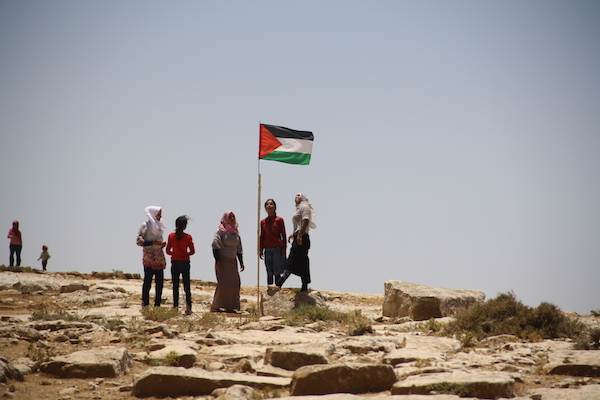 Palestinian women and girls stand around a Palestinian flag, Sumud Freedom Camp, Sarura, West Bank, May 29, 2017. (Nasser Nawajah)