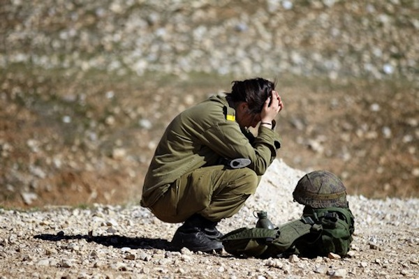 A young Israeli female combat soldier seen taking a rest after taking part in an obstacle course exercise. (Nati Shohat/Flash90)