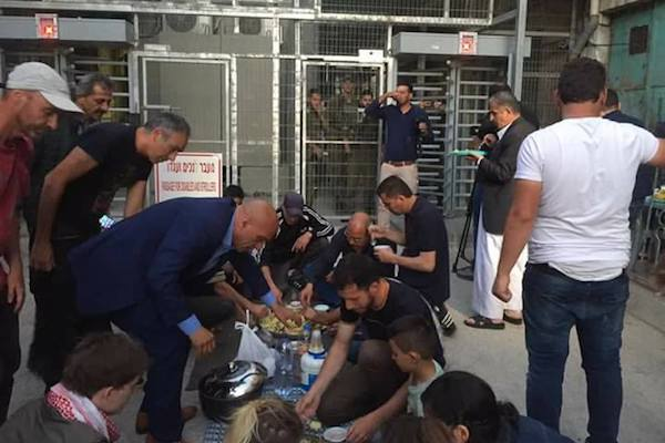 Palestinians holding an iftar meal at Tel Rumeida checkpoint, Hebron, June 3, 2017. (Courtesy of Human Rights Defenders Group)