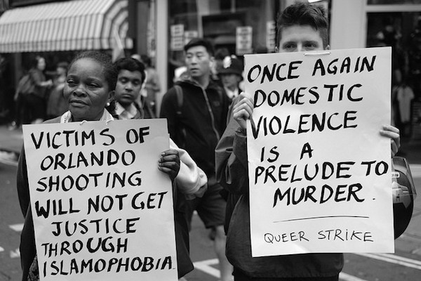 Two activists hold placards during a vigil in memory of the victims of the terror attack at an Orlando gay nightclub, London, June 13, 2016. (Alisdare Hickson/CC BY-SA 2.0)