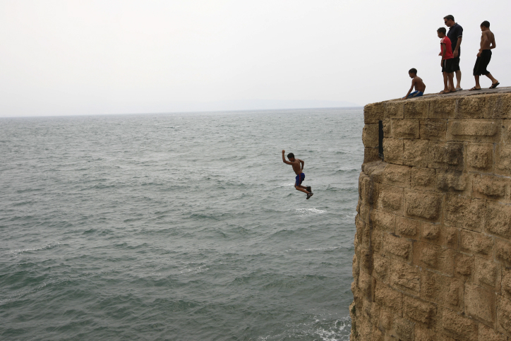 A young boy jumps off a wall into the Mediterranean Sea in Akko. (Nati Shohat/Flash90)