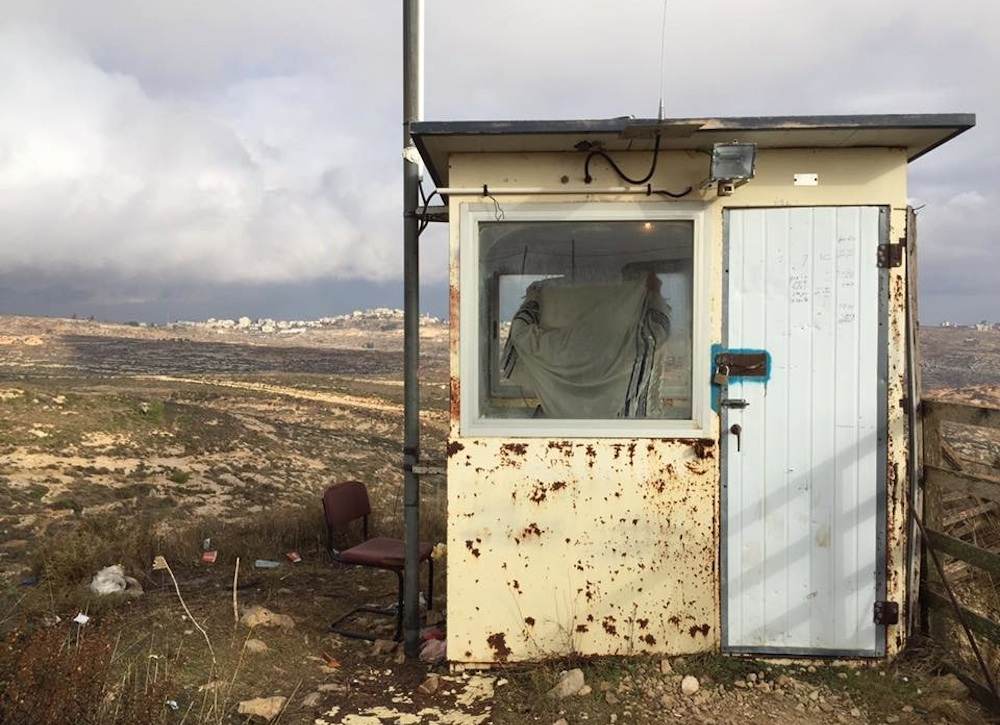 An Israeli settler draped in a prayer shawl looks out from the Amona outpost in the West Bank. (Edo Konrad)