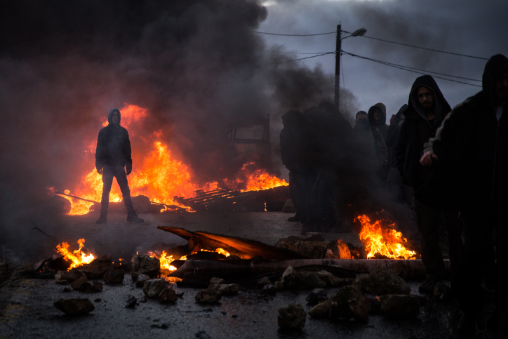 Protesters burn tires at the entrance to the illegal outpost of Amona, on February 1, 2017. (Hadas Parush/Flash90)