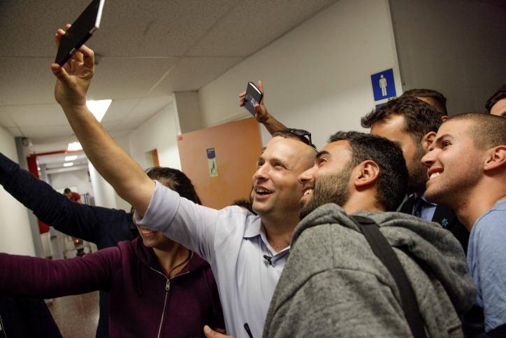 Education Minister Naftali Bennett poses for a selfie with Israeli students during a visit to Ariel University in the West Bank, March 10, 2015. (Flash90)