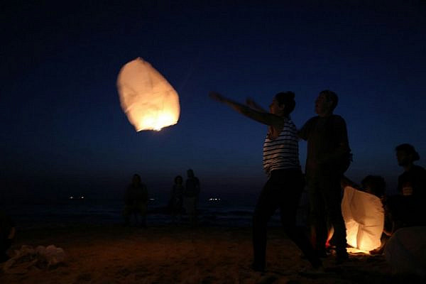 Israeli activists release paper lanterns in solidarity with blacked-out Gaza, Ashkelon beach, June 19, 2017. (Maria Zreik/Activestills.org)