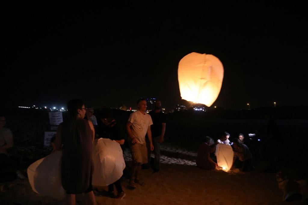 Israeli activists release paper lanterns in solidarity with blacked-out Gaza, Ashkelon beach, June 19, 2017. (Haidi Motola/Activestills.org)
