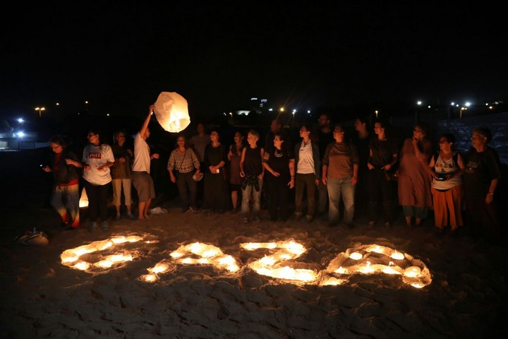 "Israeli activists write ""Gaza"" in the sand with paper lanterns during a protest in solidarity with the residents of Gaza, Ashkelon beach, June 19, 2017. (Haidi Motola/Activestills.org)"