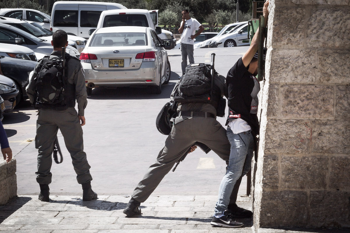 Israeli troops stop and search a young Palestinian man in East Jerusalem. (Sebi Berens/Flash90)