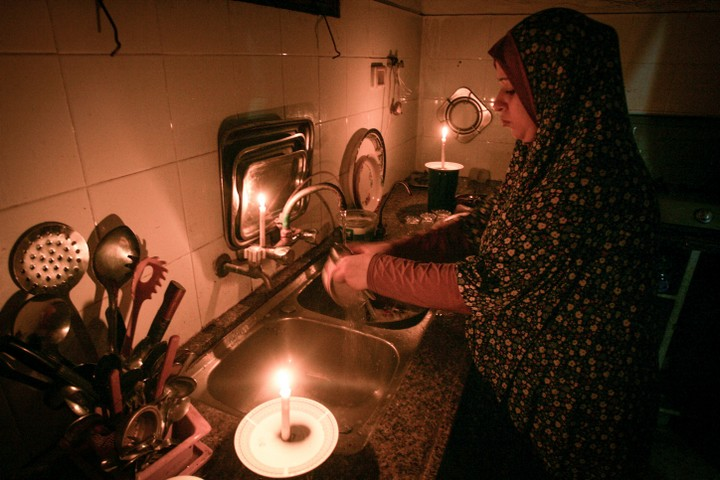 A Palestinian woman washes dishes by candlelight during a power outage in a makeshift home in the Rafah refugee camp in southern Gaza, June 12, 2017. (Abed Rahim Khatib/Flash90)