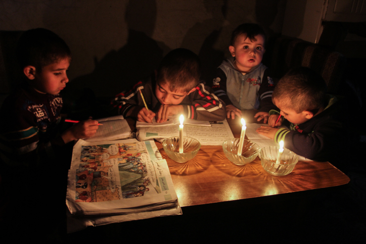 Palestinian boys study by candlelight during a power outage in Rafah, southern Gaza Strip on March 14, 2015. (Abed Rahim Khatib /Flash90)