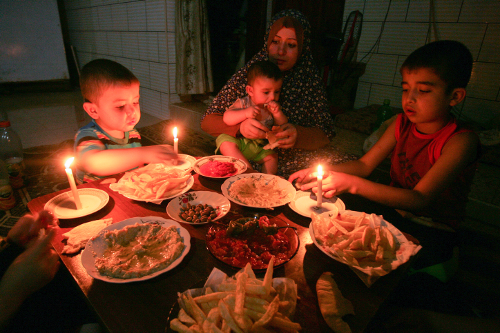 A Palestinian family eats dinner by candlelight at their makeshift home in the Rafah refugee camp, in the southern Gaza Strip, during a power outage on June 12, 2017. (Abed Rahim Khatib/ Flash90)