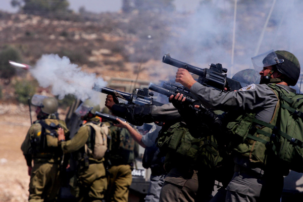 Israeli soldiers and police fires tear gas at Palestinian demonstrators during a protest against the expansion of the nearby Jewish settlement of Halamish, in the West Bank village of Nabi Saleh, near Ramallah, September 16, 2011. (Issam Rimawi/Flash 90)