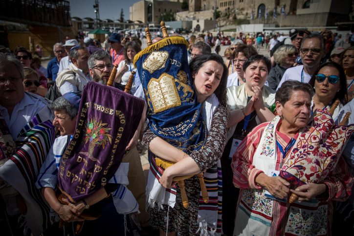 Members of the Reform and Conservative Jewish movements hold torah scrolls during a mixed prayer at the public square in front of the Western Wall, Jerusalem's Old City, May 18, 2017. (Yonatan Sindel/Flash90)
