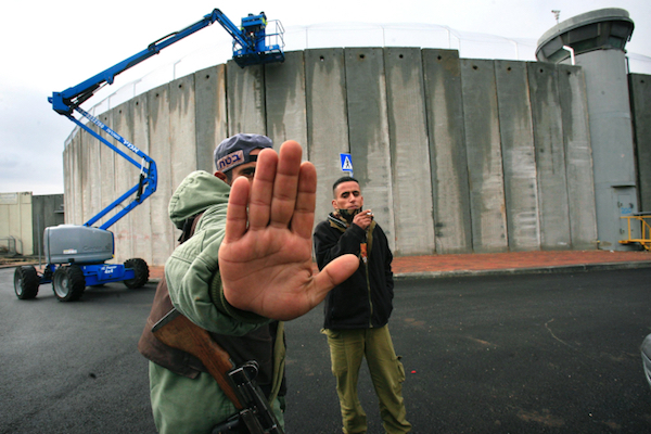 An Israeli soldier tries to prevent a photograph being taken of construction on the separation wall, Bethlehem, January 7, 2006. (Nati Shohat/Flash90)