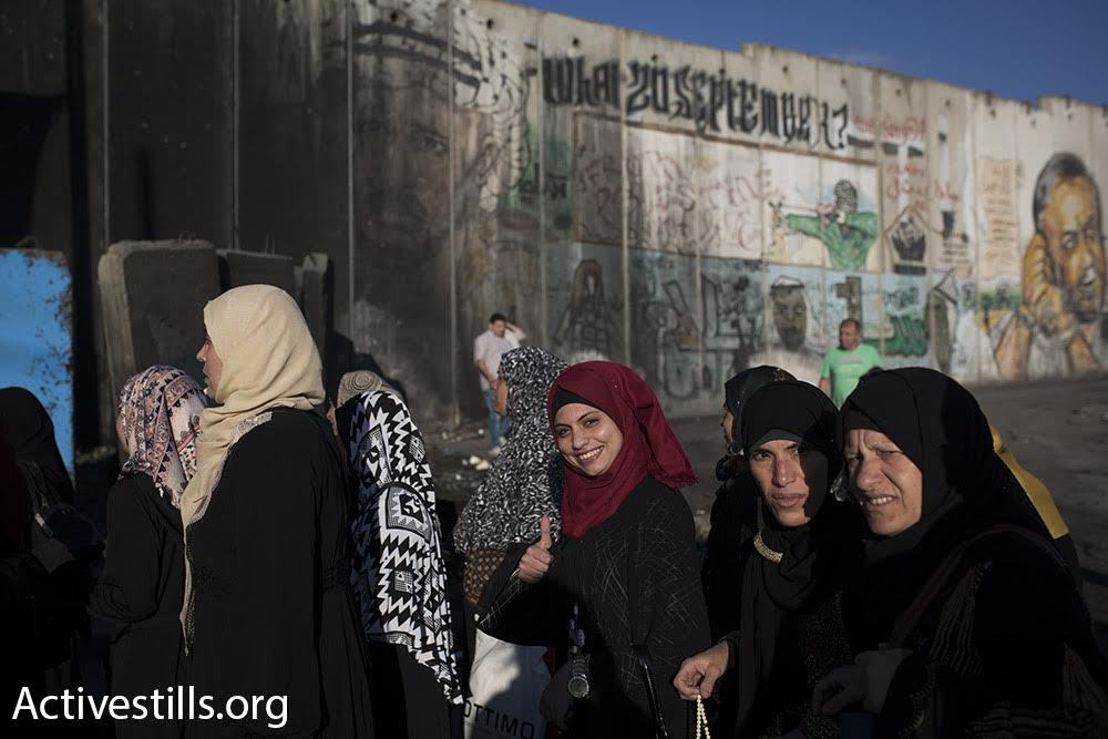 Palestinian women cross Qalandiya checkpoint into Jerusalem's A-Ram neighborhood during the first Friday of Ramadan. The Israeli authorities limited crossing to women, children, and men over the age of 40. (Oren Ziv/Activestills.org)