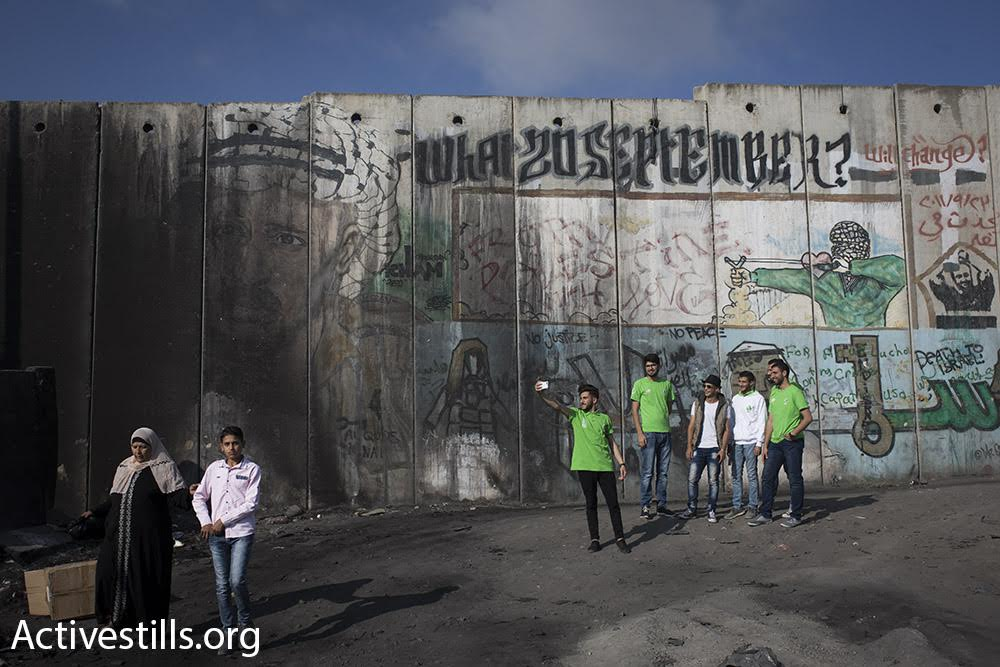Palestinian teens take a selfie with the separation wall, next to Qalandiya checkpoint in the West Bank on the first Friday of Ramadan, June 2, 2017. (Oren Ziv/Activestills.org)