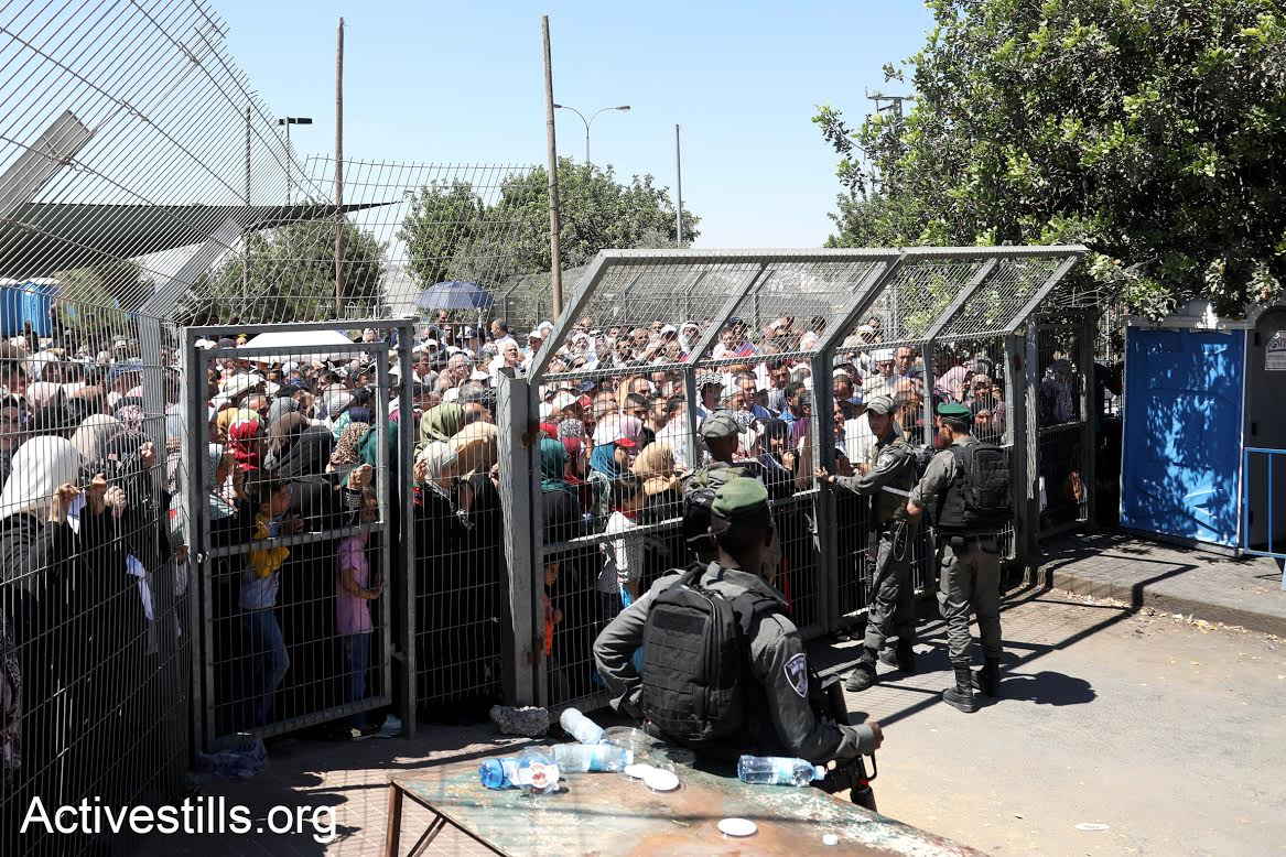 Palestinians wait in line at Checkpoint 300 outside Bethlehem on the last Friday of Ramadan, July 23, 2017. (Haidi Motola/Activestills.org)