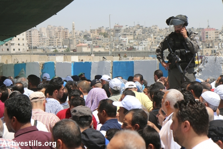 Palestinians from the West Bank cross through Qalandyia checkpoint to attend the second Friday prayers in Jerusalem's Al-Aqsa Mosque, June 9, 2017. Israeli authorities allowed women of all ages and men over 40 to enter Jerusalem without permits on Fridays during the month of Ramadan only. (Ahmad al-Bazz/Activestills.org)