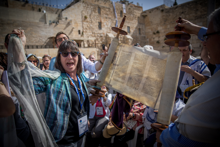 Members of the Reform and Conservative Jewish movements hold torah scrolls during a mixed men and women prayer at the public square in front of the Western Wall, in Jerusalem's Old City, on May 18, 2017. (Yonatan Sindel/Flash90)