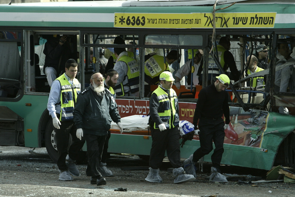 Paramedics and police carry away a victim of a suicide bombing in Jerusalem that killed eight and wounded 60 during the Second Intifada, Jerusalem, February 14, 2004. (Flash90)
