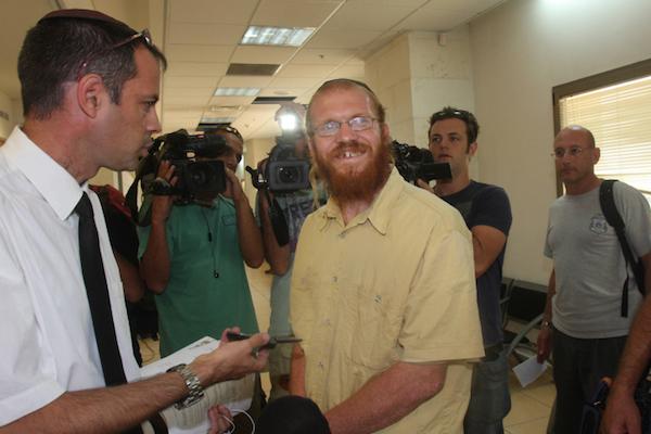 Rabbi Yosef Elitzur speaks with his lawyer in cour in 2010. (Roni Schutzer/Flash90)