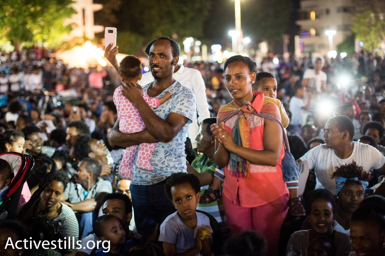 A family of asylum seekers seen during a protest against a new law to deduct wages from refugees, Tel Aviv, June 10, 2017. (Yotam Ronen/Activestills.org)