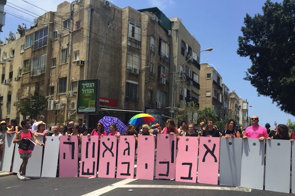 Queer anti-occupation activists block the Tel Aviv Pride Parade with signs reading: 'There's no pride in occupation', Tel Aviv, June 9, 2017. (Yael Marom)