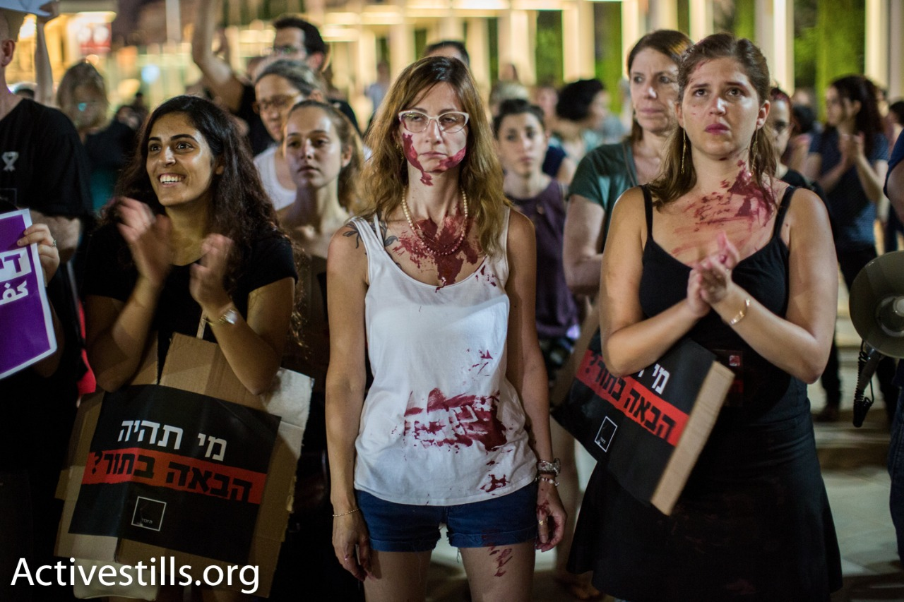 Protesters covered in fake blood protest against the murder of four women in Israel over the past week, central Tel Aviv, July 17, 2017. (Yotam Ronen/Activestills.org)