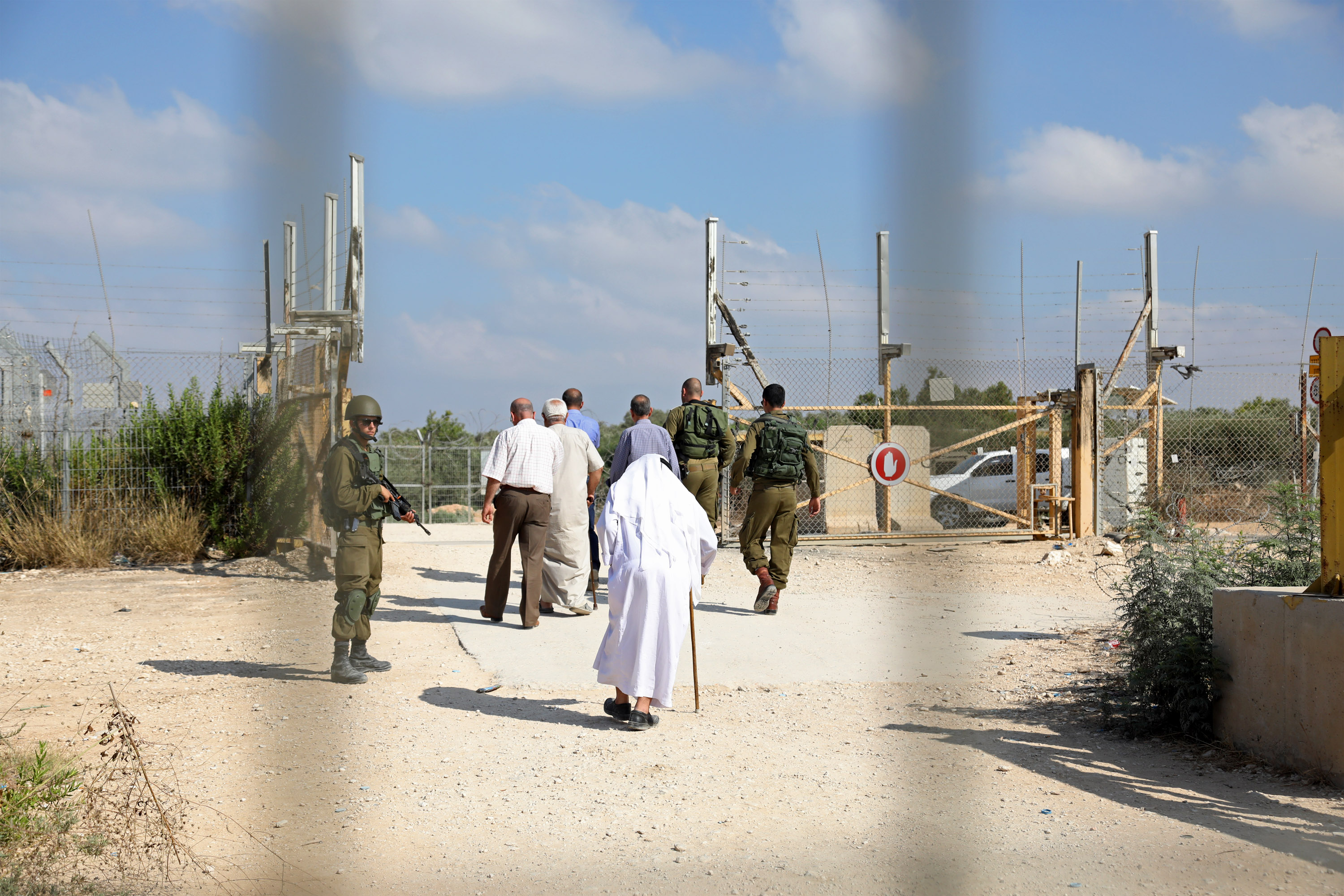 Palestinian farmers negotiate with Israeli soldiers at a military gate in the northern West Bank, demanding the Israeli army ease restrictions to allow them to more easily enter and exit, Deir Al Ghusun, July 9, 2017. (Haidi Motola/Activestills.org)