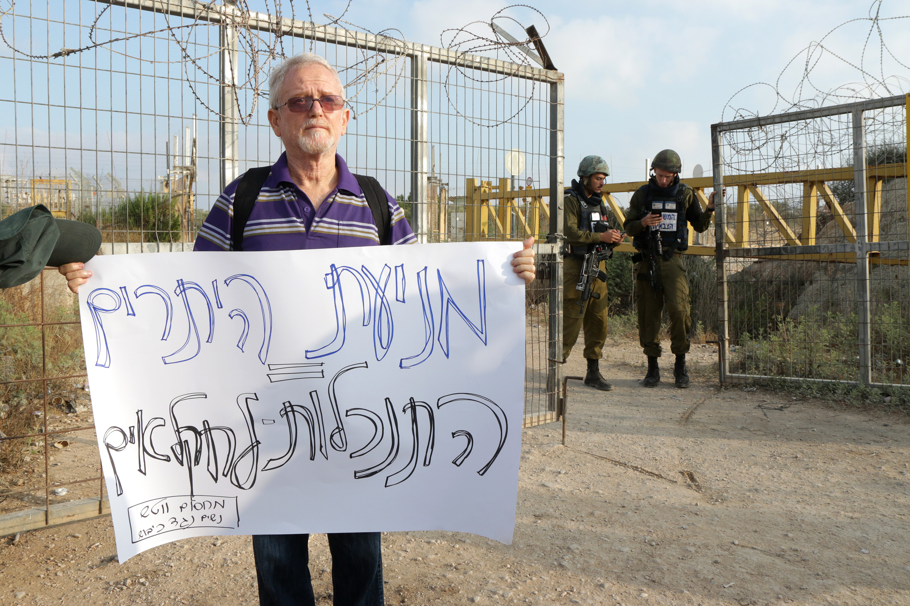 An Israeli demonstrator stands in front of Military Gate 623 during a protest to ease entry and exit for Palestinian farmers, Palestinian farmers negotiate with Israeli soldiers at a military gate in the northern West Bank, demanding the Israeli army ease restrictions to allow them to more easily enter and exit, Deir Al Ghusun, July 9, 2017. (Ahmad al-Bazz/Activestills.org)