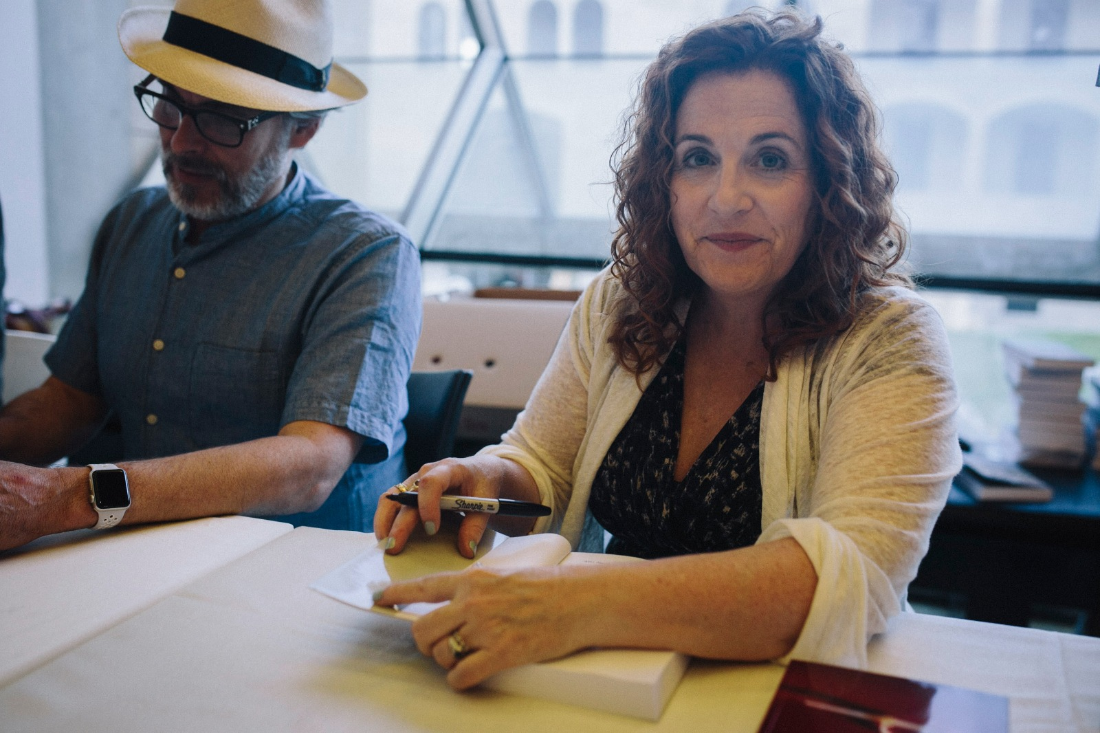 Authors Ayelet Waldman (right) and Michael Chabon sign copies of their new book, Kingdom of Olives and Ash, at a book launch event in Jerusalem. (Breaking the Silence)