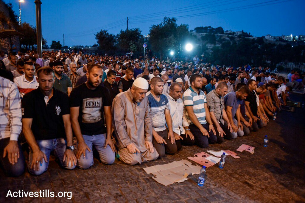 Palestinians hold a mass evening prayer adjacent to Jerusalem's Old City, July 23, 2017. (Activestills.org)