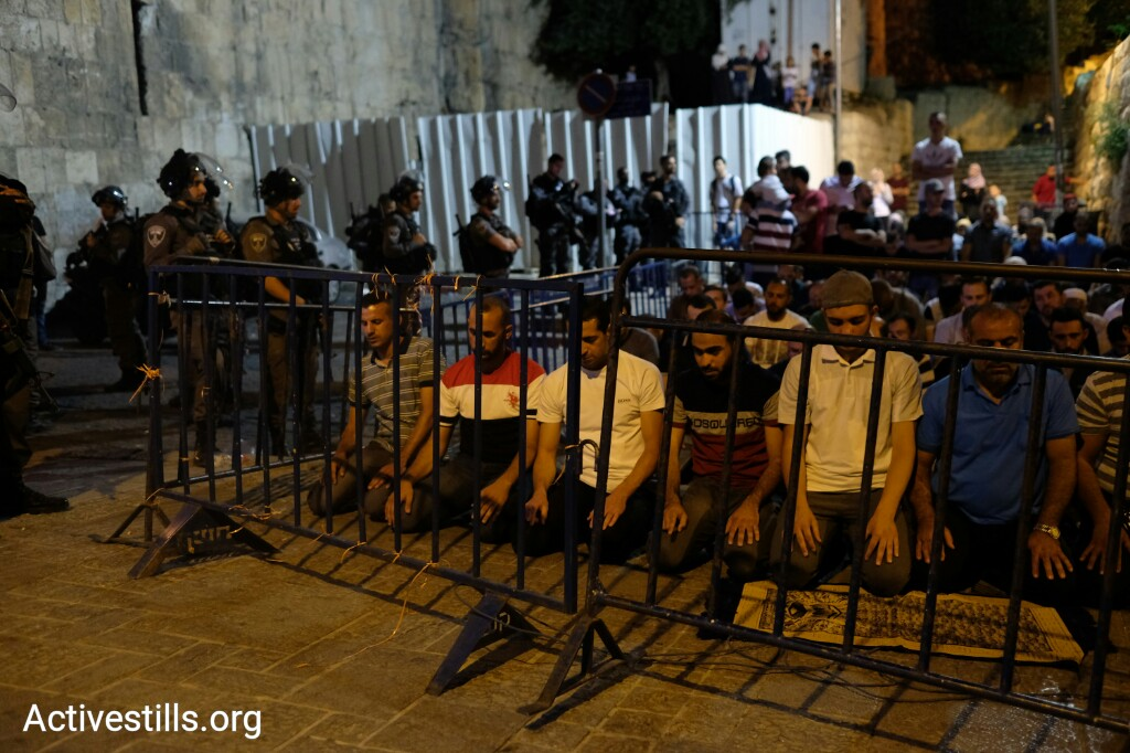 Palestinian worshippers hold evening prayers outside the Temple Mount/Haram al-Sharif compound in Jerusalem's Old City, July 16, 2017. (Activestills.org)