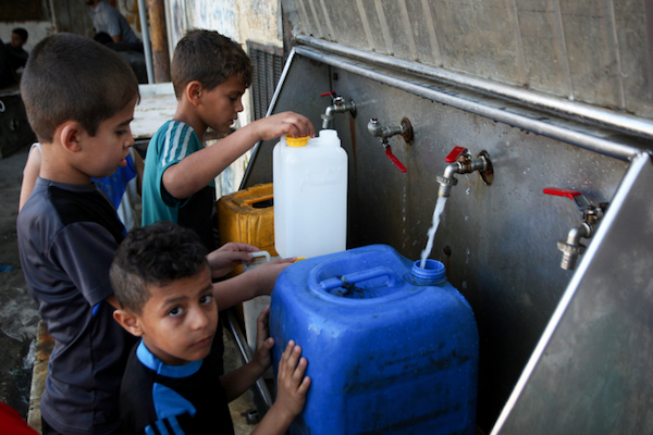 Palestinian children fill jerrycans with drinking water in the Rafah Refugee Camp in the southern Gaza Strip, June 11, 2017. (Abed Rahim Khatib/Flash90)