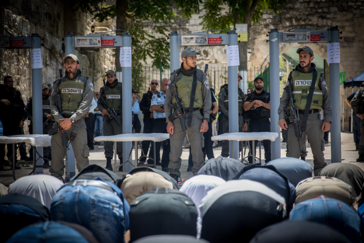Palestinian worshippers pray at Lions' Gate at the entrance to Al-Aqsa compound. Metal detectors were placed outside the site by Israeli authorities following an attack by Palestinian citizens of Israel on Israeli security forces, July 16, 2017. (Yonatan Sindel/Flash90)