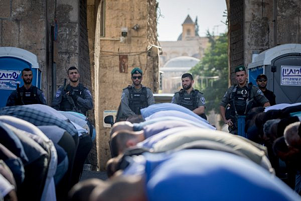 Israeli police officers guard as Muslim worshippers perform a prayer at the Lion's Gate, outside the Temple Mount, in Jerusalem's Old City. Metal detectors were placed at gates to the Temple Mount, and the Muslim worshippers refused to pass through them. The Temple Mount was reopened following last weeks terror attack when two Israeli Arabs opened fire and killed two Israeli police men. July 19, 2017. (Yonatan Sindel/Flash90