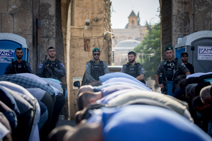 "Israeli police officers guard as Muslim worshippers perform a prayer at the Lion's Gate, outside the Temple Mount, in Jerusalem's Old City. Metal detectors were placed at gates to the Temple Mount, and the Muslim worshippers refused to pass through them. The Temple Mount was reopened following last weeks terror attack when two Israeli Arabs opened fire and killed two Israeli police men. July 19, 2017. Photo by Yonatan Sindel/Flash90 *** Local Caption *** ?? ???? ????? ????? ????? ?????? ??""? ??????? ???????"