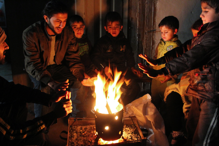 Palestinians warm themselves around a fire in Rafah in the southern Gaza Strip, on January 15, 2014, (Abed Rahim Khatib/Flash90)