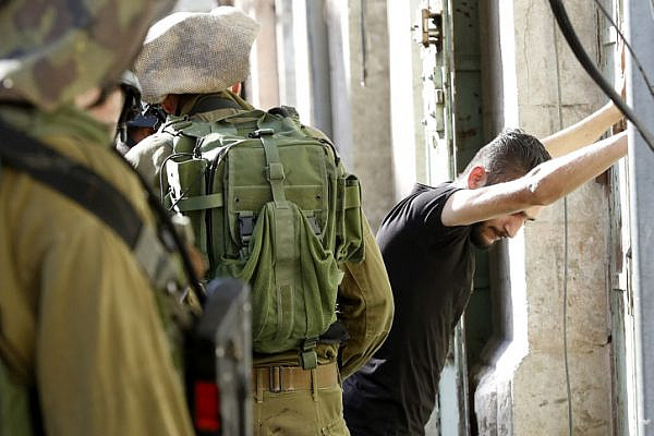 Israeli soldiers arrest a Palestinian man in the West Bank city of Hebron, on June 19, 2017. (Wisam Hashlamoun/Flash90)