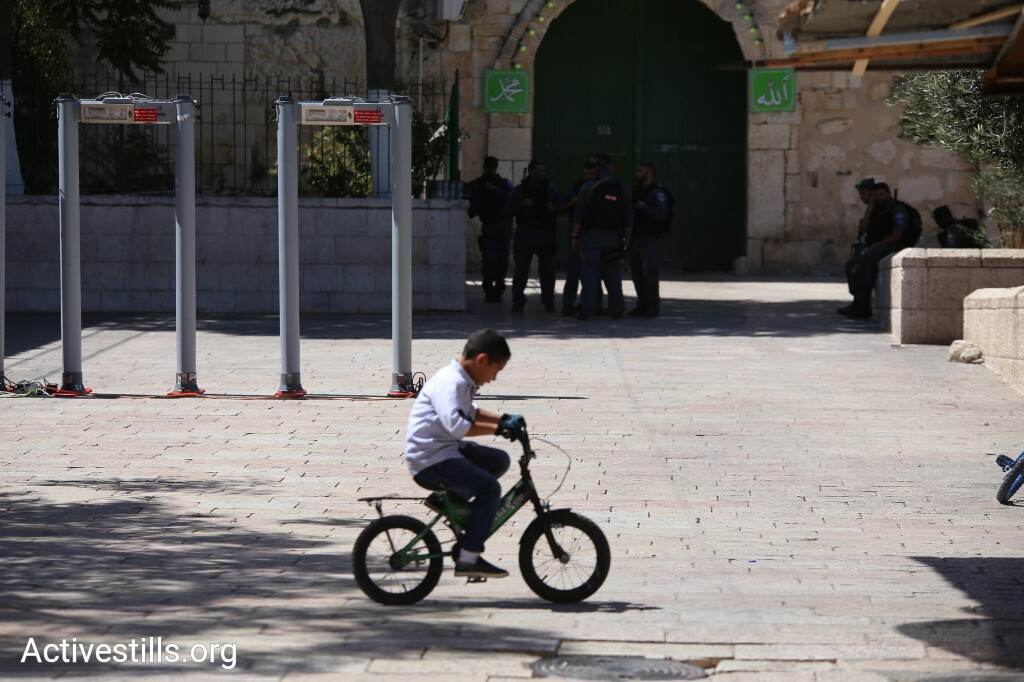 A Palestinian child rides his bike outside the Temple Mount/Haram al-Sharif. Israeli authorities erected metal detectors at the entrances to the compound in the wake of a deadly attack against Israeli security forces by three Palestinian citizens of Israel the week before. (Activestills.org)