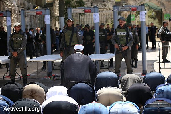 Dozens of Muslim worshippers hold a mass prayer outside the Temple Mount/Haram al-Sharif compound in Jerusalem's Old City, July 16, 2017.