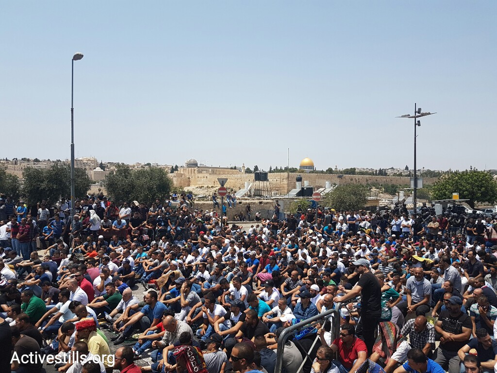 Thousands of Palestinians hold a mass prayer outside Jerusalem's Old City in the Wadi Joz neighborhood to protest the closure of the Al-Aqsa compound by Israeli authorities. (Yotam Ronen/Activestills.org)